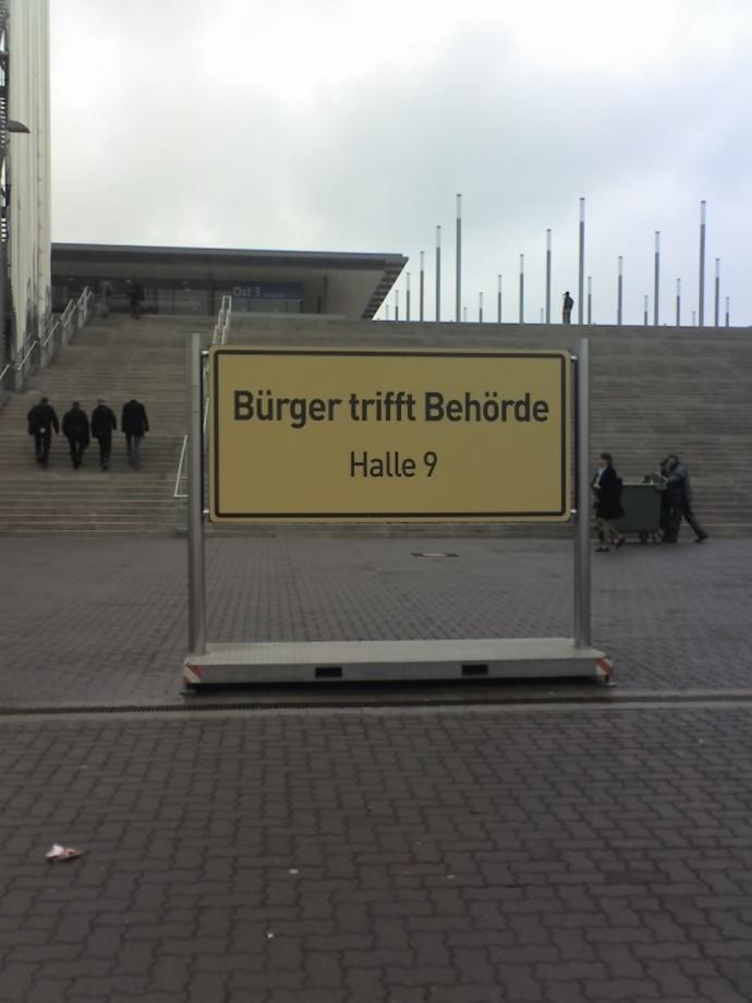 Der Ort Bürger-trifft-Behörde liegt zwischen Halle 9 und dem Dorf Genau-zwischen-die-Augen.