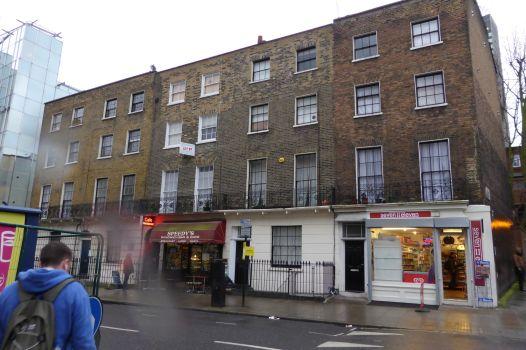 Eingerahmt von gläsernen Bürotürmen duckt sich das kleine Gebäude in der North Gower Street in die Ecke. Im Erdgeschoß: Speedys Restaurant. Für die Serie Sherlock wird die Tür rechts  ausgetauscht und das Gebäude  die Baker Street 221B deklariert.