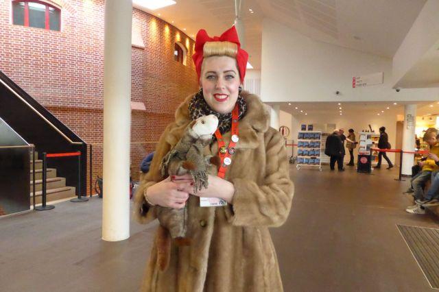 Lauren trägt die Kopfbedeckung von Witwe Bolte, einen Pelzmantel und das Wiesel.