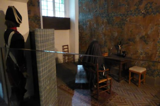 Etwas cheesy, aber ganz anschaulich: Mit Puppen nachgestellte Szene in einer Zelle  von Marie Antoinette. Sie kniet und tut Buße, hinter dem Schirm beobachten sie rund um die Uhr zwei Wächter.