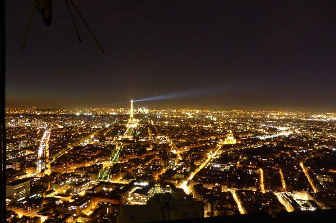 Die Stadt ist ein orangenes Gespinst in einer schwarzen See. Bild: Silencer.  (c)  Tour Eiffel – Illuminations Pierre Bideau.