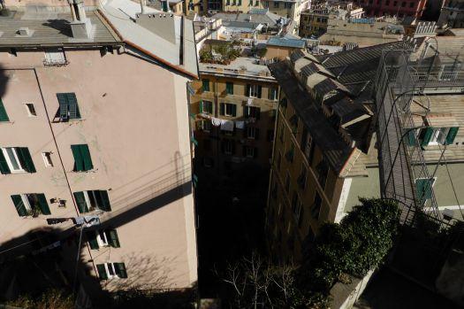 Blick von oben auf hohe Häuser, zwischen denen deren Dächern Laufstege sind.