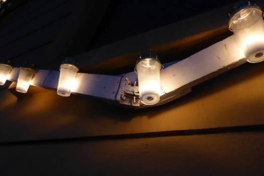 Gläser mit Kerzen drin stecken jetzt in den Metallschlingen der merkwürdigen Holzgestelle.