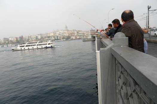 Männer stehen am Ufer und Angeln.