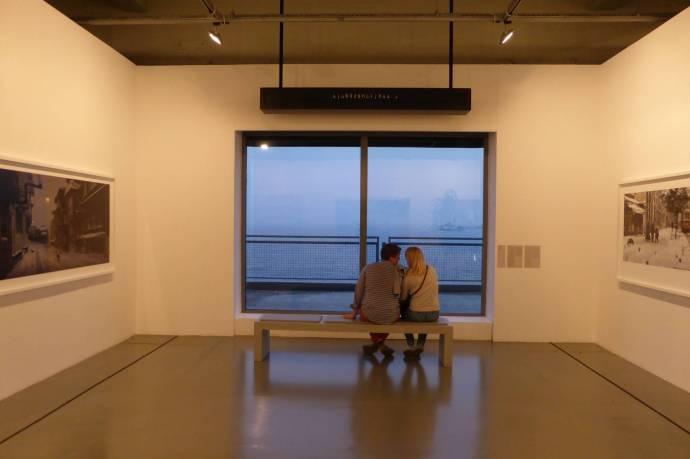 Über dem jungen Paar, selbst Besucher, rattert alle paar Sekunden ein Schild und zeigt verschiedene Destinationen an. So sieht es aus, als ob die hier auf ein Schiff oder einen Bus warten. So werden zufällige Besucher, die hier Platz nehmen, Teil des Kunstwerks.