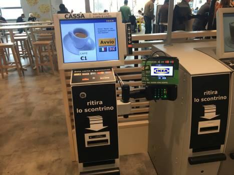 Wie in italienischen Bars, aber mit IKEA-Automatisierung: Man sucht am Touchscreen aus was man trinken will, bezahlt es per Karte und geht mit dem Beleg an die Bar, wo die Barrista den Caffé zubereitet.